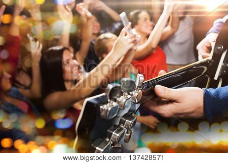 holidays, music, nightlife and people concept - close up of musiciab playing electric guitar on stage over happy people crowd taking picture by smartphones and waving hands at concert in night club