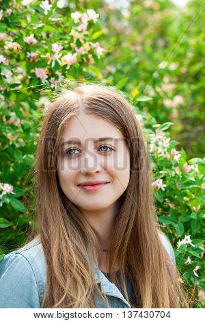 Portrait of a young beautiful girl of Caucasian appearance with very beautiful eyes. Girl on a background of a blossoming tree outdoors in the summer. Amazing eye color.