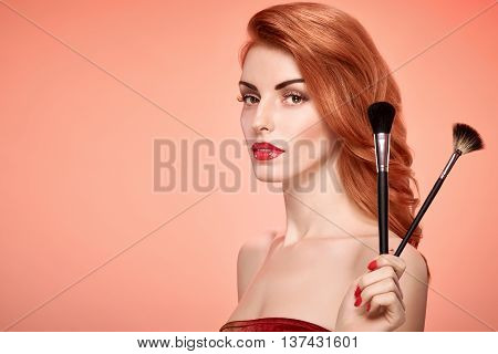 Fashion. Redhead Model woman with Makeup brushes. Natural makeup. Beauty portrait sexy girl. Shiny wavy Hairstyle, fashion Makeup, Eyelashes, Perfect skin. Skincare Spa concept. Creative unusual look