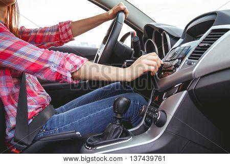 Car dashboard. Radio closeup. Woman sets up radio