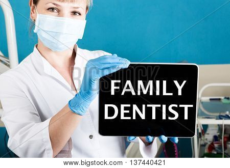 technology, internet and networking in medicine concept - femail dentist holding a tablet pc with family dentist sign. at the dental equipment background.