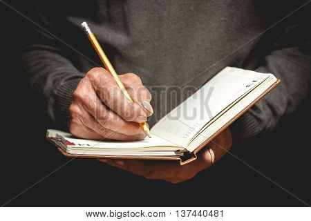 An elderly man wrote in pencil in a notebook. Photo in low key