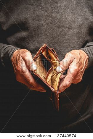 Empty wallet in the hands of an elderly man. Poverty in retirement concept poster