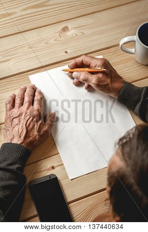 The old man wrote a testament, sitting at a wooden table