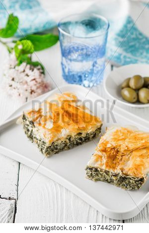 Greek pie spanakopita on the white plate with accessorizes vertical