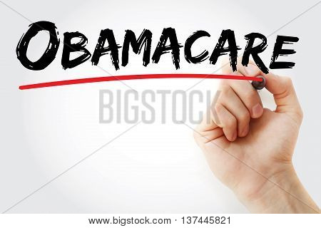 Hand Writing Obamacare With Red Marker