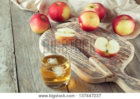 glass of juice and apples on a cutting board closeup