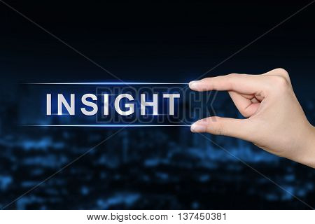 hand pushing insight button on blurred blue background