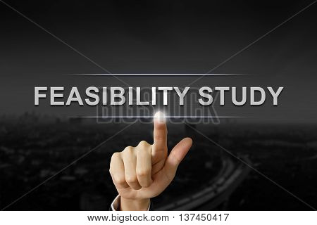 business hand clicking feasibility study button on black blurred background
