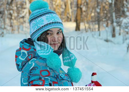 young brunette girl in a blue jacket, blue cap with patterns and pompons on the background of a winter forest, her hair covered with frost
