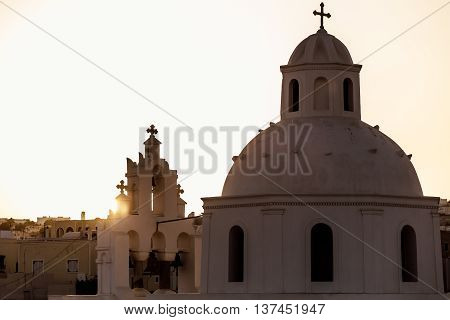 silhouette of a typical church in the Greek islands in the sunset light