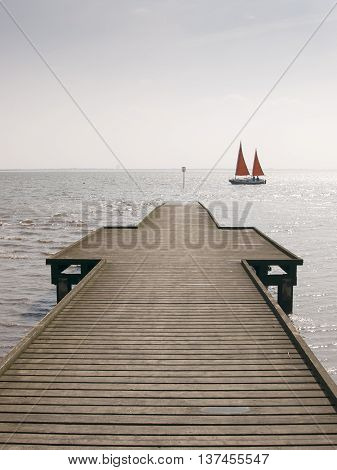 Wooden Jetty and yacht in sail at sea