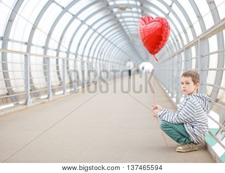 boy with red heart sitting on the sidelines. sad child sits on his haunches and holding a red balloon in the shape of a heart. expectation of dating, waiting for love. copy space for your text