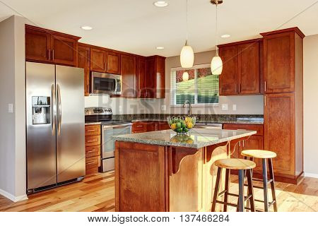 Spacious Kitchen Room With Bar, Stainless Steel Appliances And Pendant Lights.
