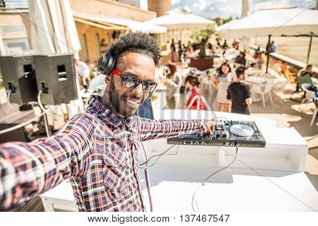 Dj taking a selfie while mixing music on a deejay set in a club people dancing