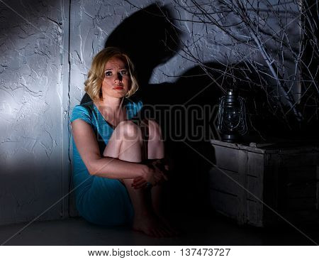 Frightened Young Woman With Extinct Lamp Sitting In Dark Horrible Place