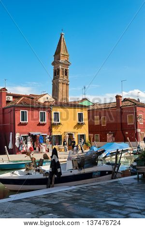 VENICE, ITALY - 17 OCTOBER 2015: Boats and colorful houses on Burano, Venice, Italy with tourists walking alongside the canal and the leaning campanile of San Martino behind
