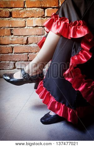 Close up view of legs of woman sitting on a chair and dressed in costume of Flamenco dancer. The photo has deliberately darkened edges. Vertically.