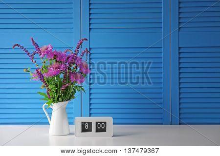 Beautiful wildflowers bouquet on blue folding screen background