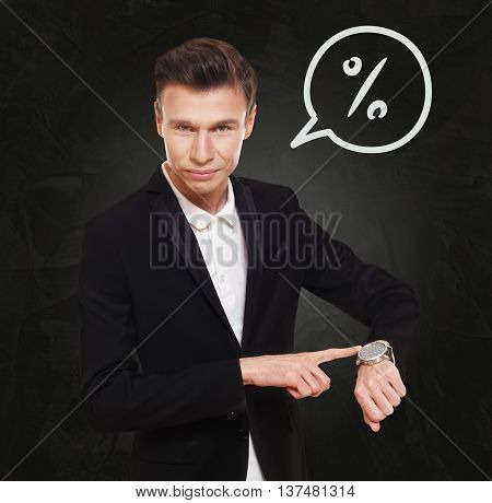 Time is money. Businessman point at his watch showing banking concept. Man in suit with watch at black background, thinking cloud with percent, interest rate sign. Financial business, bank deposit