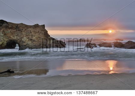 Sandy coves and rocky cliffs of the Pacific Ocean. Sunset at Pescadero State Beach, California