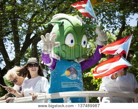 NEW YORK - JUNE 12 2016: Participants and mascot for the Arecibo Observatory wave flags and celebrate on a float in the 59th annual National Puerto Rican Day Parade on 5th Ave in NYC, June 12 2016.