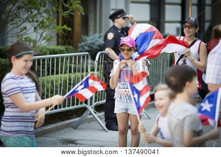 NEW YORK - JUNE 12 2016: A young girl celebrating wears a Puerto Rican flag as a cape at the 59th annual National Puerto Rican Day Parade along 5th Avenue in New York City on June 12 2016.