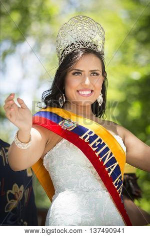 NEW YORK - JUNE 12 2016: A beauty queen from Columbia wearing a jeweled tiara waves to the crowd from a float in the 59th National Puerto Rican Day Parade on 5th Ave in New York City on June 12 2016.