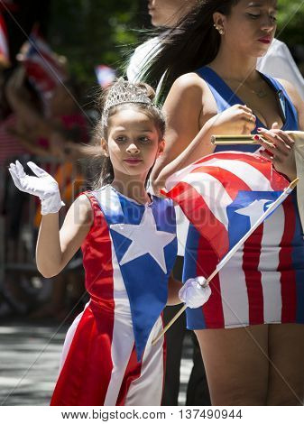 NEW YORK - JUNE 12 2016: A young beauty queen wearing a Puerto Rican flag dress and jeweled tiara waves to the crowd at the 59th National Puerto Rican Day Parade on 5th Ave in NYC, June 12 2016.