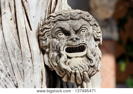 A tragic mask in the hand of Statue of Melpomene the muse of tragedy on the balcony of Achillion princess Sissy's palace on greek island Corfu in Greece.