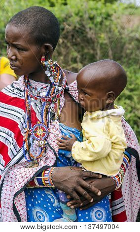 AFRICA, KENYA, MAY, 05, 2016 - Maasai tribe woman with traditional piercings and beadwork with a small baby on hands in Maasai Mara National Park, Kenya