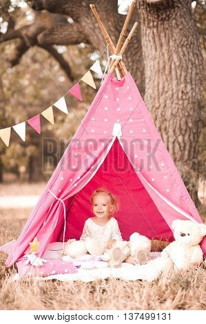 Smiling kid girl 2-3 year old playing in wigwam outdoors. Looking at camera. Childhood.