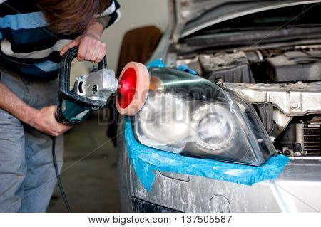 Mechanic Cleaning Headlights And Polishing With Power Buffer Mac