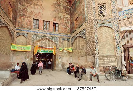 ISFAHAN, IRAN - OCT 16, 2014: Many customers and women in traditional hijab walking near brick building of Old Market in historical persian city on October 16, 2014. Isfahan is the 3rd largest city of Iran