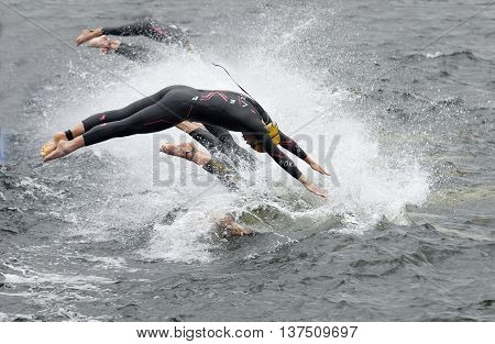 STOCKHOLM - JUL 02 2016: The female competitors wearing yellow bathing cap jump into the water after the start signal in the Women's ITU World Triathlon series event July 02 2016 in Stockholm Sweden