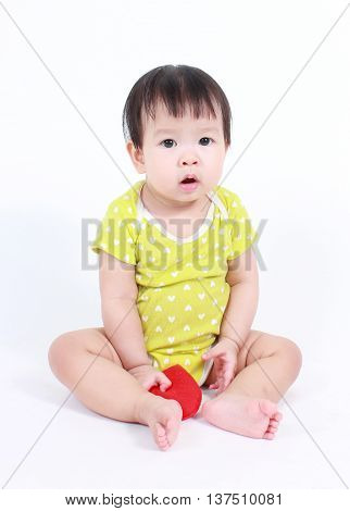 Beautiful child, cute baby holding a red heart isolated on white.