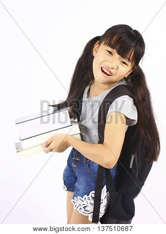 Portrait of little asian girl holding the books with her backpack, back to school.