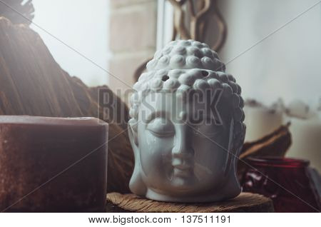 Zen spiritual ritual meditating white head of Buddha brown candle on dark windowsill background. Religion concept esoterics. Still life rustic style. Home decor. Place for text copy space. Film tonal effect vintage.