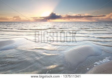 sunset on Ijsselmeer lake coast Friesland Netherlands