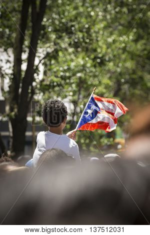 NEW YORK - JUNE 12 2016: A young boy celebrating waves a flag during the 59th annual National Puerto Rican Day Parade along 5th Avenue in New York City on June 12 2016.