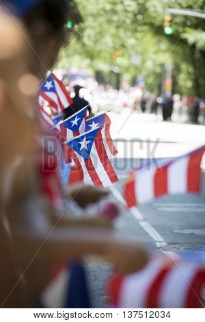 NEW YORK - JUNE 12 2016: Puerto Rican flags held by spectators celebrating the 59th annual National Puerto Rican Day Parade along 5th Avenue in New York City on June 12 2016.