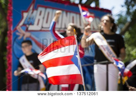NEW YORK - JUNE 12 2016: A Puerto Rican flag waves in front of the float for the character La Borinquena, the new superhero at the 59th National Puerto Rican Day Parade on 5th Ave in NYC June 12 2016.