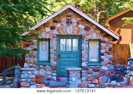 Rustic mountain cabin made of rocks and stones surrounded by Pine Trees