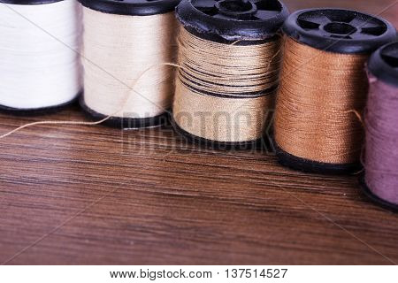Reels Of Brown Cotton On A Wooden Surface