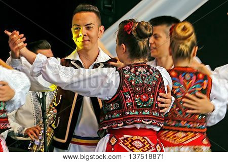 ROMANIA TIMISOARA - JULY 6 2016: Young Romanian dancers in traditional costume perform folk dance during