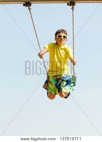 Boy Playing Swinging By Swing-set.