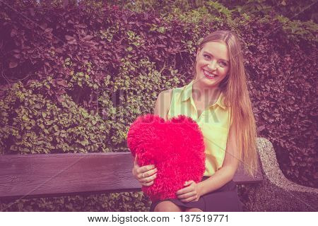 Love and feelings. Happy enamoured woman sitting on bench with big red heart in hands. Beautiful smiling girl in park.
