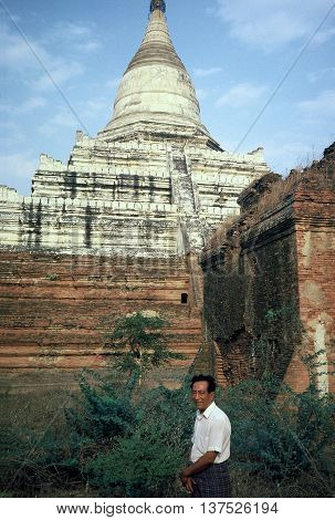 PAGAN / MYANMAR - CIRCA 1987: A gentleman smiles for a photograph in front of the ancient Shwesandaw Buddhist Pagoda in Pagan.