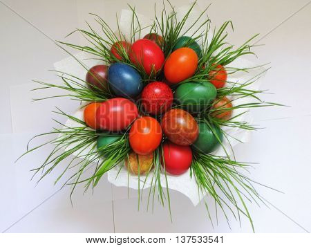 Colored natural easter eggs in a basket on white background