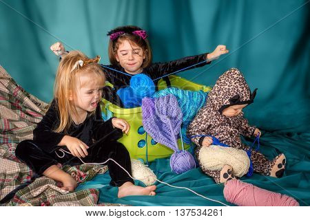 Three young girls dressed up in cat costumes play with yarn and knitting projects.